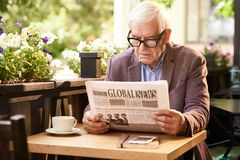 Senior Man Reading Newspaper in Outdoor Cafe Stock Images