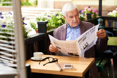 Senior Man Reading Newspaper on Outdoor Terrace in Cafe. Portrait of modern senior man reading newspaper in cafe outdoors enjoying sunny morning in retirement Royalty Free Stock Images