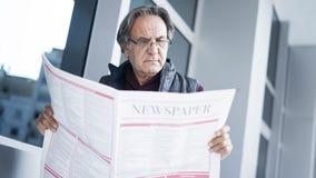 Senior man reading newspaper in outdoors Stock Image
