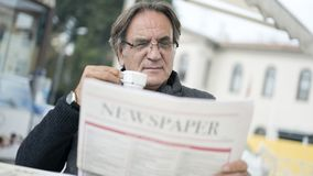 Senior man reading newspaper in outdoors Stock Photography
