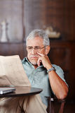 Senior man reading newspaper in retirement home Stock Photo