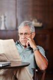 Senior man reading newspaper in retirement home stock photo