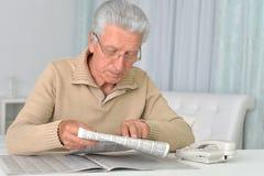 Senior man reading newspaper Stock Images