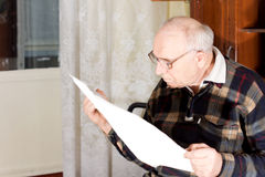 Senior man reading a newspaper. Senior man wearing glasses sitting in his living room reading a newspaper Royalty Free Stock Photography