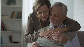 Senior man reading newspaper, woman coming from behind to hug, family morning