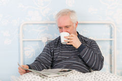 Senior man reading newspapers in bed Stock Image