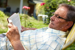Senior man reading outdoor. Healthy looking senior man is his late 70s sitting in garden at home and reading book, outdoor Stock Photo