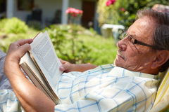 Senior man reading outdoor. Healthy looking senior man is his late 70s sitting in garden at home and reading book, outdoor Stock Image