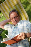 Senior man reading outdoor. Healthy looking senior man is his late 70s sitting in garden at home and reading book, outdoor Stock Photography