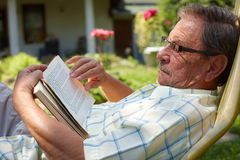 Senior man reading outdoor. Healthy looking senior man is his late 70s sitting in garden at home and reading book, outdoor Royalty Free Stock Images