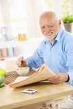 Senior man reading papers at breakfast. Smiling senior man sitting in kitchen reading papers while having cereal for breakfast Royalty Free Stock Photos