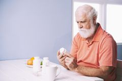 Man checking recommendations. Senior man reading recommendations on bottle of tablets royalty free stock image