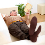 Senior man reading on sofa Royalty Free Stock Image