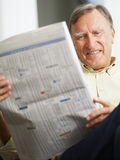 Senior man reading stock listings Royalty Free Stock Image