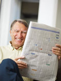 Senior man reading stock listings. And smiling Royalty Free Stock Images
