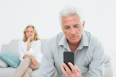 Senior man reading text message with woman at  home Stock Photos
