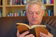 Senior man reads in front of bookcase stock images