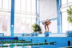 Senior man ready to jump in the swimming pool. Senior man in an indoor swimming pool. Active pensioner enjoying sport. An old man ready to jump in the pool Stock Photos