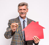 Senior man. Realtor is holding a key and model of house stock photos