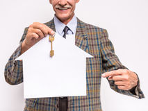 Senior man. Realtor is holding a key and model of house royalty free stock images