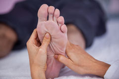 Senior man receiving foot massage from physiotherapist Royalty Free Stock Images