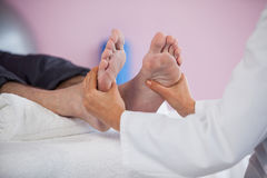 Senior man receiving foot massage from physiotherapist Royalty Free Stock Photo