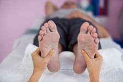 Senior man receiving foot massage from physiotherapist Royalty Free Stock Image