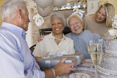 Senior Man Receiving Gift From Friends Stock Image