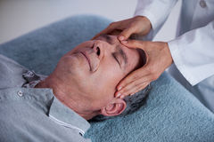 Senior man receiving head massage from physiotherapist Stock Image
