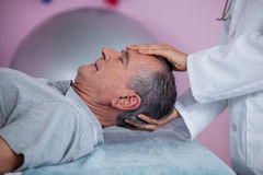Senior man receiving head massage from physiotherapist Stock Photos