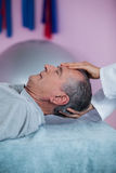 Senior man receiving head massage from physiotherapist Stock Images