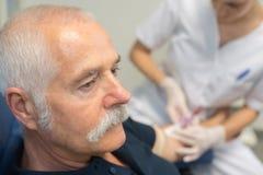 Senior man receiving insulin injection Stock Image