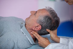 Senior man receiving neck massage from physiotherapist Stock Image