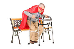 Senior man with red cape standing up with walker Royalty Free Stock Photo