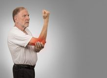 Senior man with red elbow inflammation suffering from pain. Closeup senior man with elbow inflammation colored in red suffering from pain and rheumatism isolated Royalty Free Stock Photos