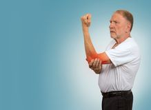 Senior man with red elbow inflammation suffering from pain. Closeup senior man with elbow inflammation colored in red suffering from pain and rheumatism isolated Royalty Free Stock Image