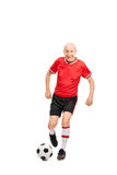 Senior man in a red jersey playing football Stock Images