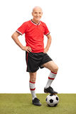Senior man in a red jersey stepping over a football Royalty Free Stock Photos