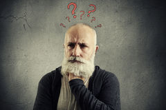 Senior man with red question marks above the head. Portrait of despondent senior man with red question marks above the head over grey background royalty free stock images