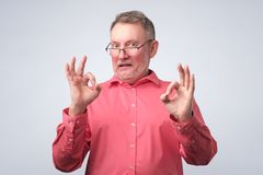 Senior man in red shirt showing OK sign stock images