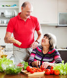 Senior man in red and  woman cooking  together Royalty Free Stock Photos