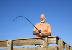 Senior Man Reels in Fish Stock Photo