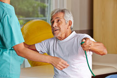 Senior man at rehab with nurse. Senior men at rehab with nurse pulling on a string Royalty Free Stock Photos