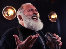 Senior man rejoices while singing in the vintage silver microphone isolated in studio. Close-up of senior man rejoices while singing in the vintage silver royalty free stock photo