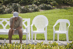 Senior man relaxing. Senior man sitting on a bench with his hand on his chin Royalty Free Stock Photos