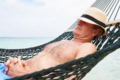 Senior Man Relaxing In Beach Hammock Stock Photo