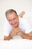 Senior Man Relaxing On Bed Stock Photography