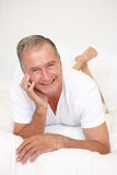 Senior Man Relaxing On Bed Stock Photos
