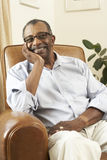 Senior Man Relaxing In Chair At Home Stock Image