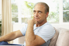 Senior Man Relaxing In Chair At Home Stock Photography
